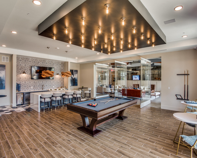 A luxury apartment that includes a game room with billiards, by Hensley Lamkin Rachel, Inc.