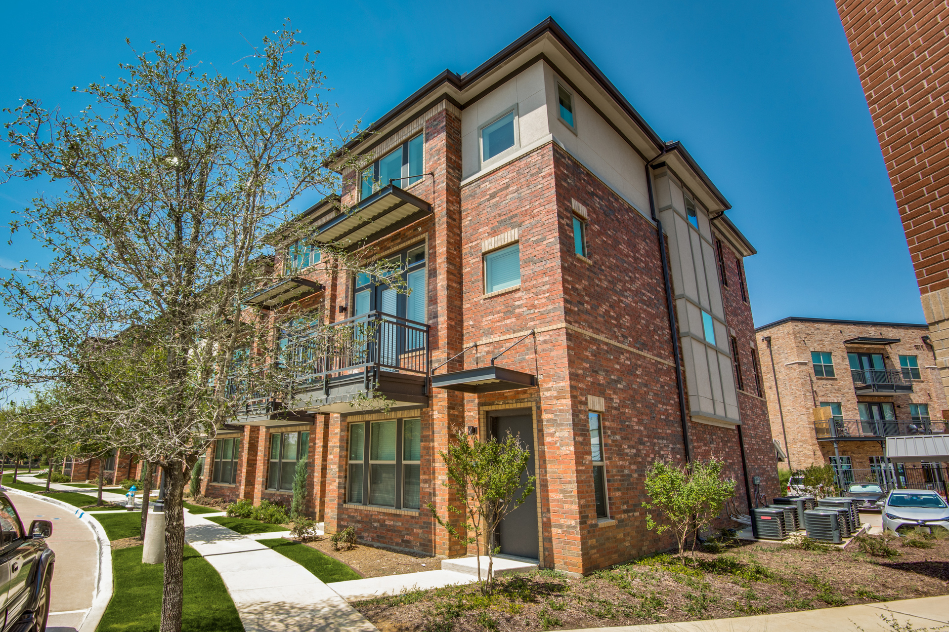 The exterior of Hillstone River Walk luxury apartments and townhomes in Flower Mound, Texas, by Hensley Lamkin Rachel, Inc.