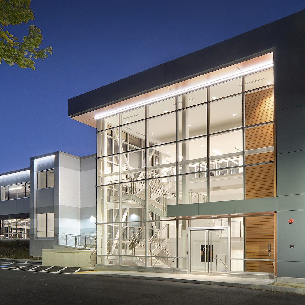 The exterior of the 54 Middlesex Turnpike located in Bedford, MA.  With complete exterior modernization, elevators within a 3-story glass atrium opened accessibility to all floors. Seventy parking places were added to maximize the property without environmental disturbance, by Dacon.