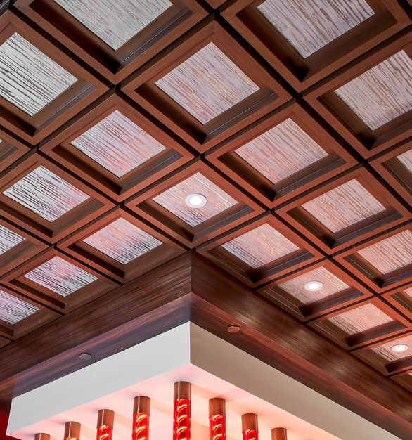 Close up view of The Madison Ceiling Tile. The tile features a custom silver metallic wall covering that perfectly accents the surrounding woodgrain finish.