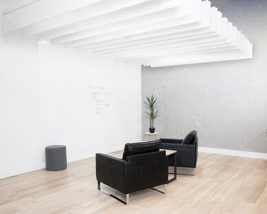 Made with 60% recycled PET materials, 40% new material, non-toxic, non-allergenic, non-irritant, no-coatings/sprays that degrade, MPS Acoustics Straight Ceiling Baffle are shown in this open office lounge space.