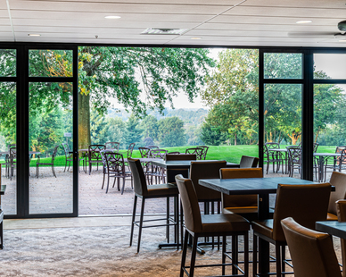 The dark bronze aluminum matches the original building while the door blends in seamlessly with the rest of the country club's style which adds to its functionality, this space has a beautiful, aesthetic appeal.