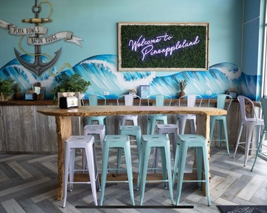 Reclaimed wood from old barns, surfboards that hang from the ceiling, large murals of waves and other decors that will make you feel like you're at the beach at Playa Bowls in Baton Rouge.