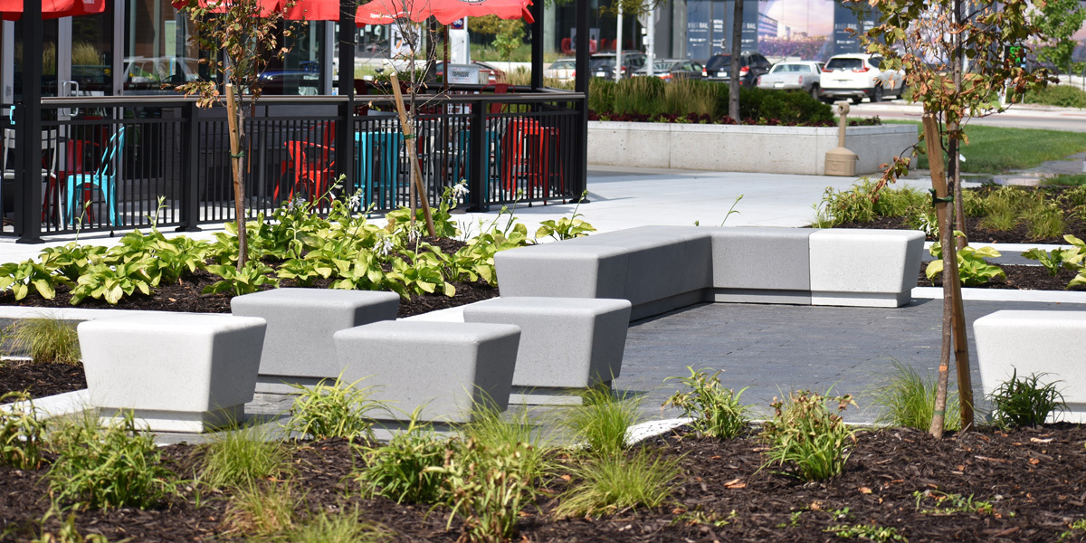 """Wausau Tile's Our Town helped create a space with a flexible design component for an already finished space. The smooth, rounded surface of Our Town benches with acid wash finish and a combination of colors provides a fabric friendly surface. The long term low maintenance of precast and sheer weight of concrete was sure to keep each piece in place and always ready to use. The modular design of the Our Town collection allowed for pod space designed for """"together yet apart"""" social distancing or for small groups and family gatherings."""