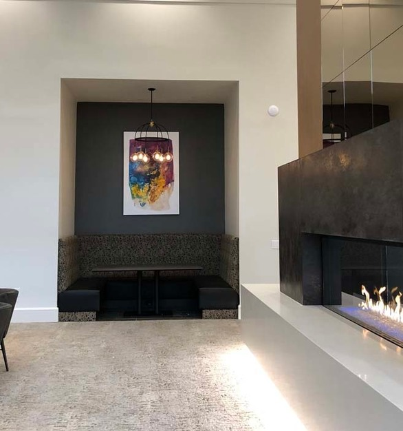 The fireplace is the undeniable focal point of this clubroom in Alexan Exchange, a Houston-area, luxury apartment complex. Beautifully skinned in our versatile, stylish Oxide porcelain tile panels, this double-sided wonder gets lucky residents and guests fired up year-round in this elegant hub for gathering, dining, and entertaining.