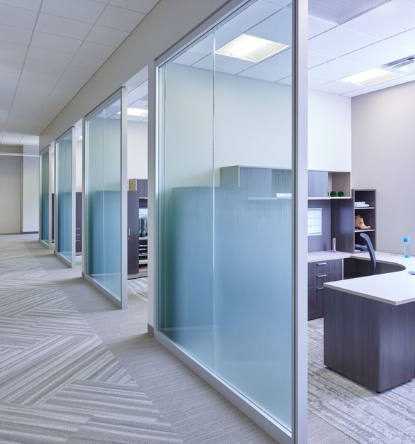 A mixture of low workstation panels and clear and custom-etched glass walls provides a continuous flow of natural light, creating a bright, open environment for collaboration and innovation between team members and departments.