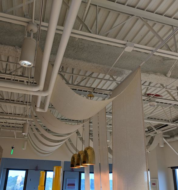 Ceiling curtains within the work lounge at the Evereve office. This full kitchen provides space for officewide lunches.