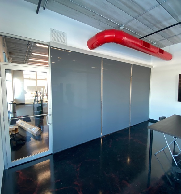 The chic, grey color of American Drapery Systems commercial roller shades was the perfect addition to this office conference room.