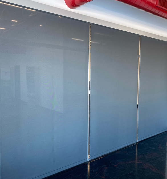 Rolling commercial shades are sleek and easy to use and work perfectly in a conference room.