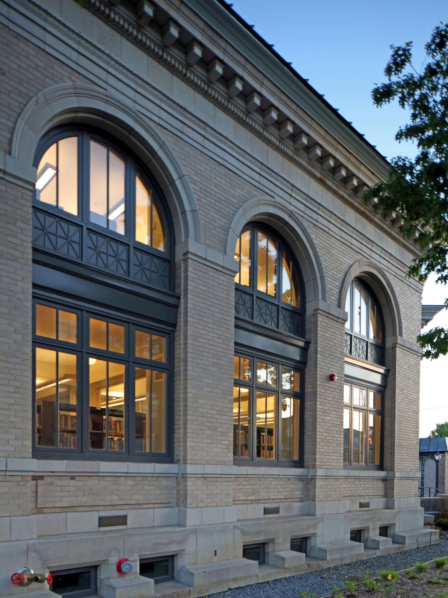 The exterior of the Gloversville Public Library was renovated with aluminum-clad wood casement, awning and fixed windows in a variety of shapes and sizes. One of the building's most striking features are the reading nooks on the upper floors concentrated at the crown of arch-top windows that rise as much as two full stories.