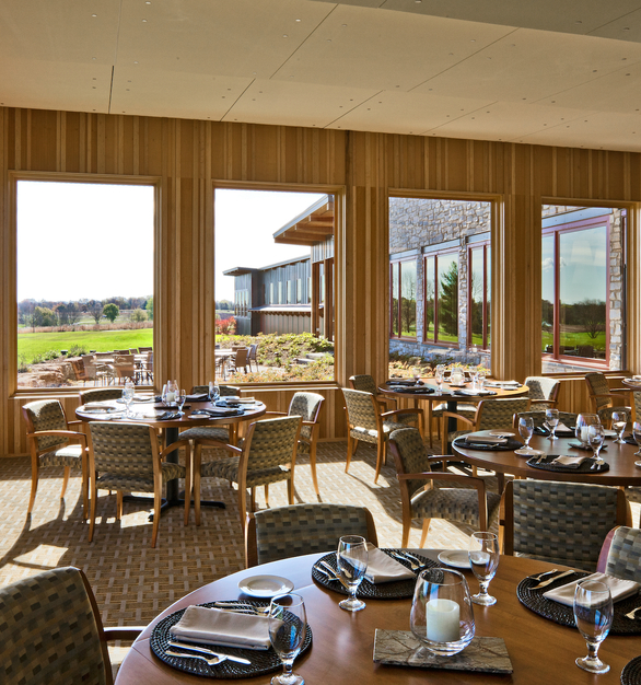 The naturally lit dining area at the Hazeltine National Golf Course Clubhouse featuring the Andersen® A-Series windows with a pine finish.