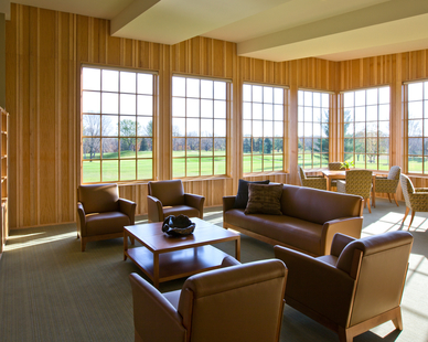 A comfortable lounge room featuring natural wood walls and comfortable seating allows guests to meet and gather. Andersen® provided their A-Series windows with grilles to blend with the architecture.