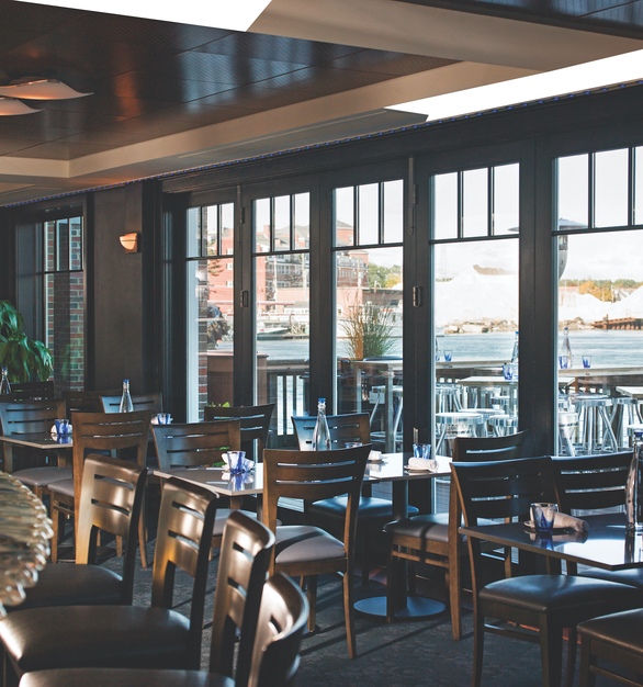 Restaurant dining interior design featuring the Andersen® Outswing Folding Doors. When open, these moving glass walls fold up to beautifully frame your view. When closed, they create a stately wall of light.