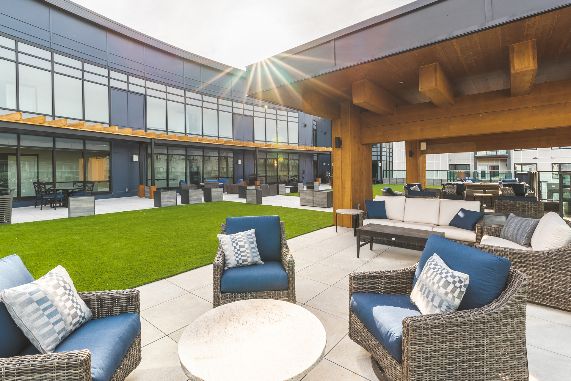 """Located in Regina, the capital of Saskatchewan, Canada, the Williston in Harbour Landing is a gorgeous, luxury apartment complex for senior living. The housing complex offers several amenities, including shops, a hair salon & nail spa, fitness centre, sports pub, and wonderful outdoor areas including the 9,000 square foot rooftop terrace, which uses Archatrak's 24""""x24″ porcelain pavers in color Calstone, as well as MIXY 60 planters and planter benches. The community gathering space cleverly uses green turf to give the rooftop a 'green' feel."""