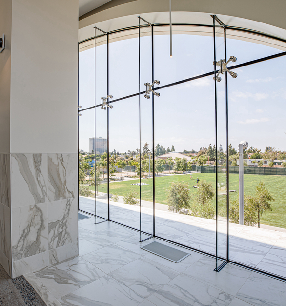 The arched structural glass wall provides stunning views and natural light for library visitors. Guests can sit and relax while reading a book and taking in the landscaping of the park and courtyard below.