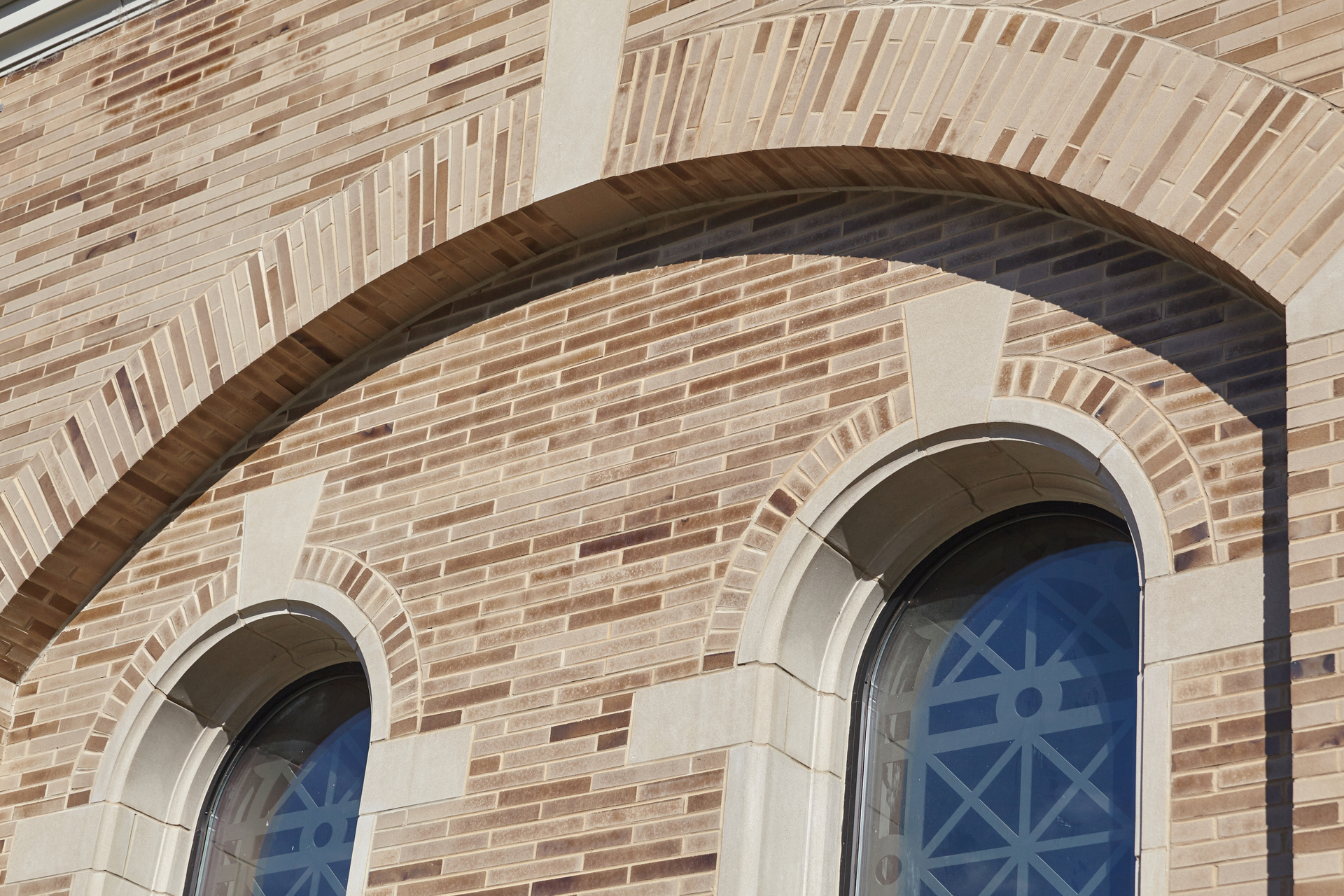 A close-up exterior view of the cathedral shows the detail of the window sculptures and smooth multi-colored bricks.  Photo by Kaminski Studios.