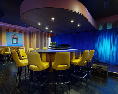 Near the stage can be seen a private dining table to enhance the customer's experience. Archuity was the architect on this project. 