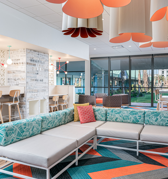 The Downtown Minimalist 5-Light Chandelier, in a lively Watermelon finish, was selected to highlight the renovated front desk area and welcome visitors with a fun, unique look. To complement these chandeliers, the Bubble Stem Mount Pendant Light was used with White glass and a Mint finish for a mid-century-style ceiling. This glass style softens the illumination slightly imbuing the space with warmth.