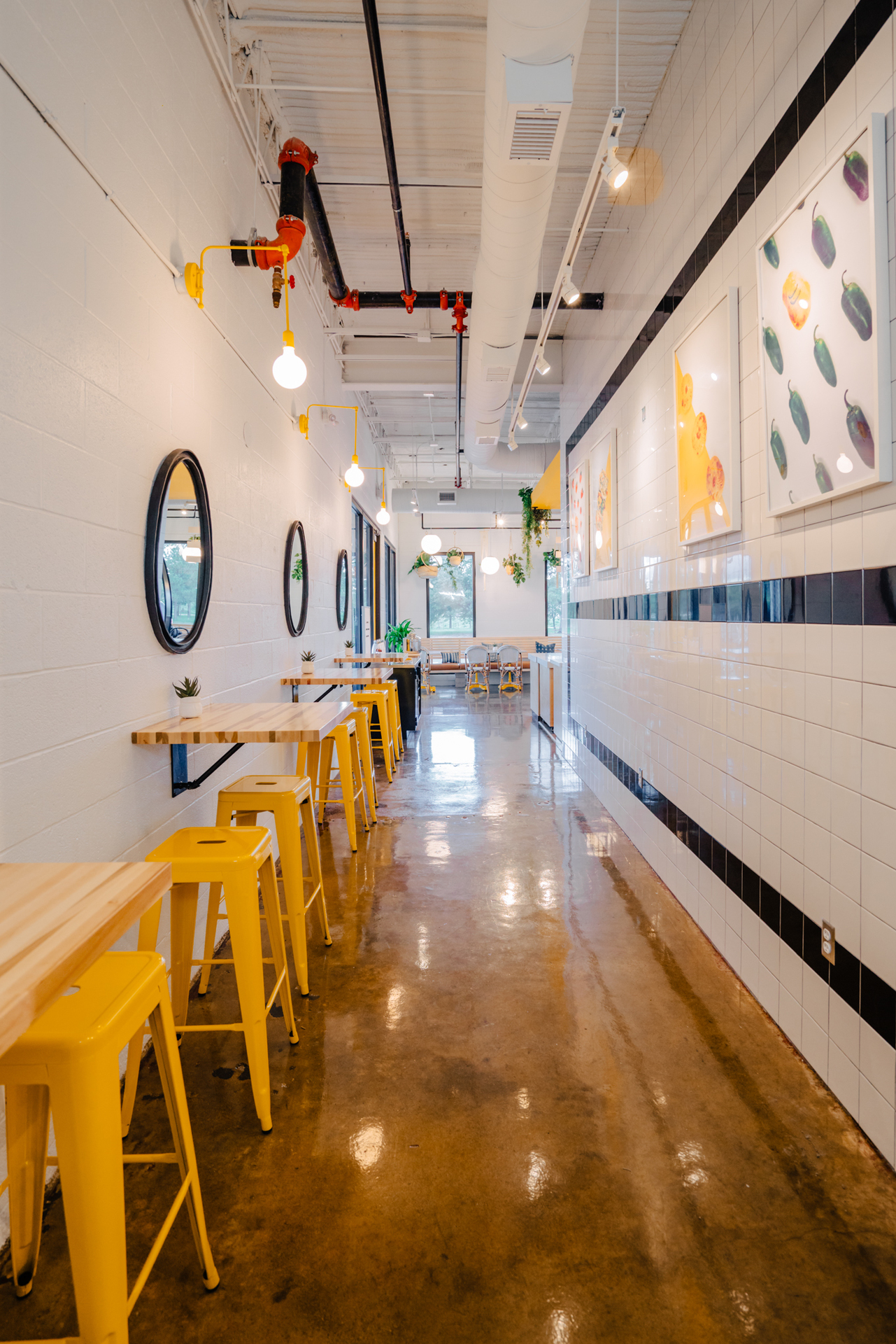The yellow color accents and bright finishes expose guests to the energetic atmosphere at EggHaus in Houston, TX, featuring the Downtown Swing Arm Sconce in buttery yellow by Barn Light Electric.