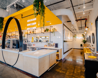 The bright and vibrant interior of EggHaus in Houston, TX, features Barn Light Electric's Downtown Swing Arm Sconce in buttery yellow to match the accent colors of the space.