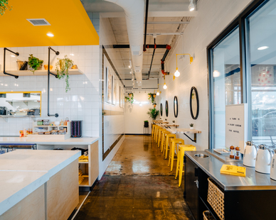 A clean and energetic interior finish at EggHaus in Houston, TX, featuring Barn Light Electric's Downtown Swing Arm Sconce in buttery yellow.