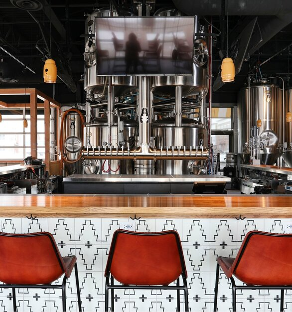 The Mig Pendant Light was selected to highlight the bar area. These industrial-style ceiling lights were customized in a high-gloss, porcelain enamel Yellow finish and black cords. The Mig Pendant is repurposed from steel acetylene tank tops to create a one-of-a-kind ceiling light. Easy to customize with more than 40 finish colors and multiple cording options.