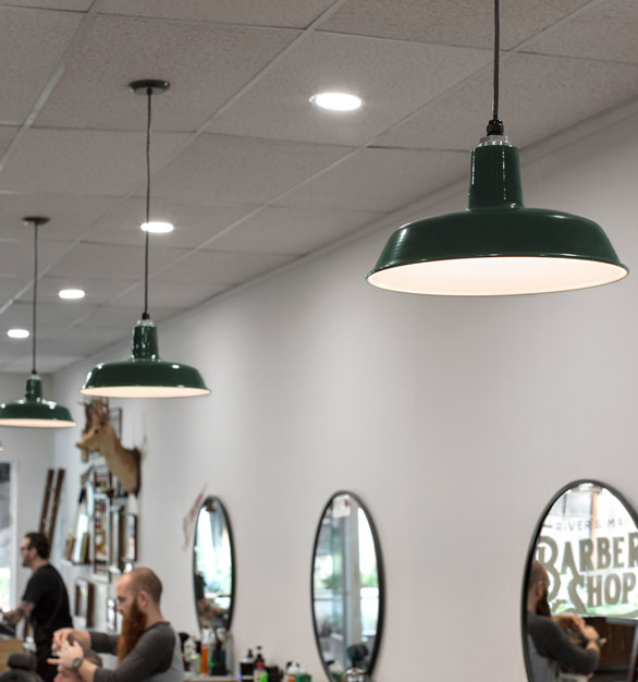 The attention to detail of Barn Light's Original Warehouse Pendants ties every interior design together. River & Main Barber Shop chose the dark green color because it matched with the mid-century look throughout the space.