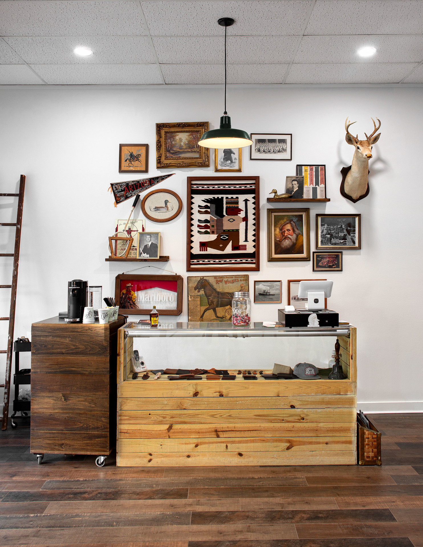 The cozy and relaxed atmosphere with eclectic artwork and wood floors at River & Main Barber Shop in Titusville, FL, featuring The Original™ Warehouse Pendant.