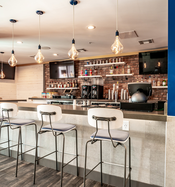 Over the nearby bar, the design team chose the sleek, modern look of the Downtown Minimalist Cord Pendant. These pendants are customized with a Navy finish and gold-and-white cloth cords that add a hint of color and texture to the space.