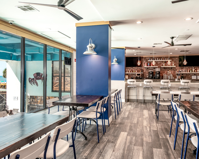 The ground-level space was completely gutted and redesigned by the talented team from Interior Quality Designs. Patrons are greeted with rustic wood flooring, pops of cobalt blue, and expansive windows with views to the beach and beyond.