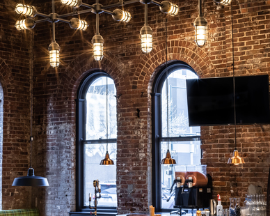 Similar to the Vanguard Chandelier, these custom American-made, industrial-style fixtures feature 18 cast-guard-and-glass lights with a Textured Black finish and ribbed glass.