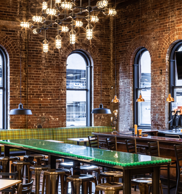 Communal tables in the center of the space offered an opportunity for a more dramatic visual element. Barn Light Electric's team of engineers created a custom chandelier by expanding a standard chandelier to a 9-foot long, 3-foot high jewel suspended over the tables.