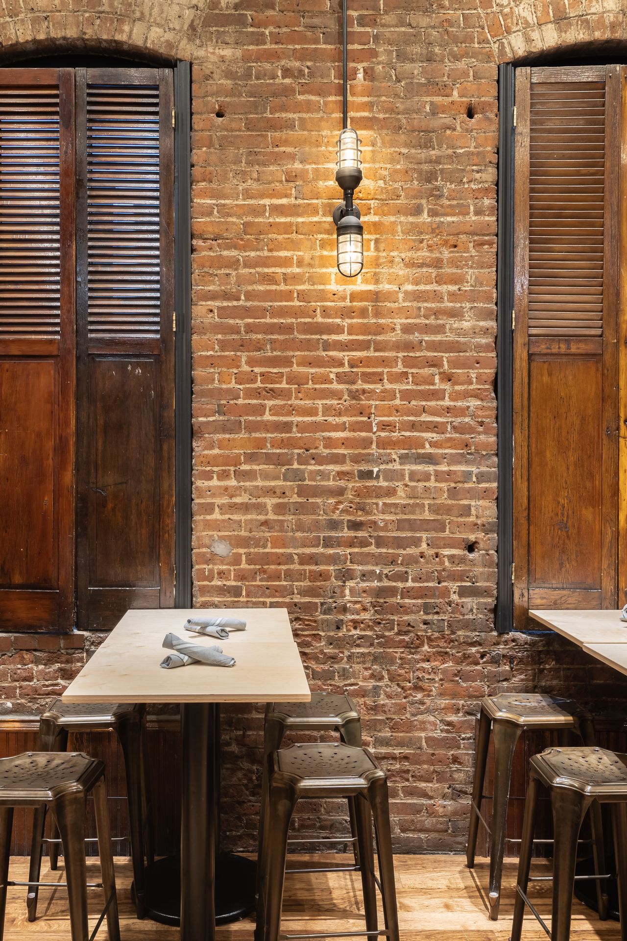 Along the walls, more industrial lights highlight the texture of the old brickwork. Atomic Topless Double Industrial Guard Sconces, customized with standard cast guards, Textured Black finish, and ribbed glass, cast a soft glow over the bricks while maintaining the industrial vibe.
