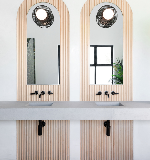 Double concrete sinks are accented with gorgeous solid wood tambour panels behind the mirrors.