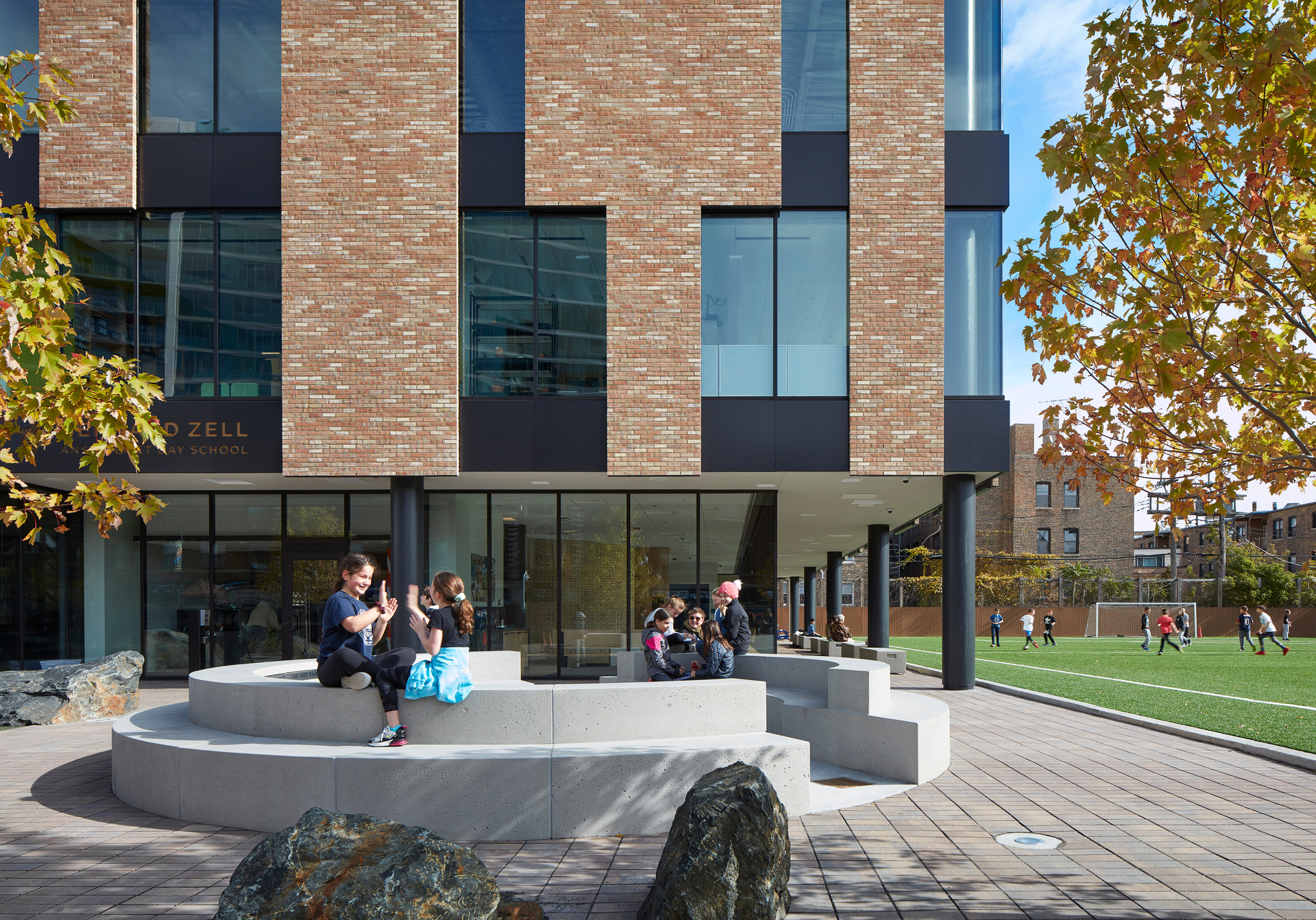The outdoor entryway and courtyard provide a perfect space for students, visitors, staff and faculty to relax and connect with each other. The brick facade school expansion is placed next to the outdoor soccer field and just behind the courtyard.  Photo by Steve Hall, Hall + Merrick Photographers