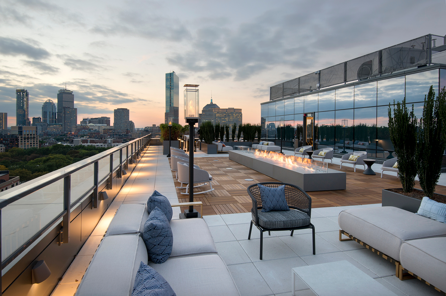 Some of 345 Harrison apartment's amenities include comfortable, modern seating and a twelve-person firepit with glass details that express the building's upscale vibe. Bison 2x2 Smooth Ipê Wood Tilesover Bison Versadjust Pedestals were specified for many of the modern rooftop spaces to provide modularity.
