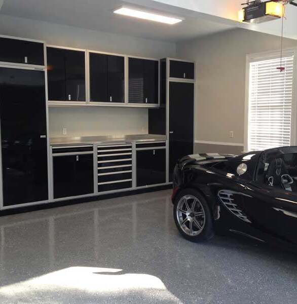A residential garage showcasing black Moduline PROII™ Series aluminum cabinets to complete this custom design.