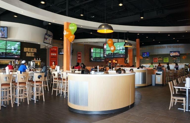 Lighting above the reception desk at this Buffalo Wings and Rings restaurant showcases the Beretto light provided by Bock Lighting.