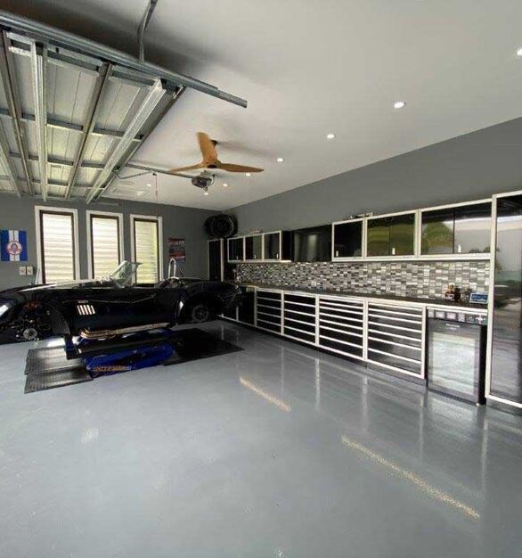 A Shelby cobra residential garage with black PROII™ Series Moduline Cabinets.