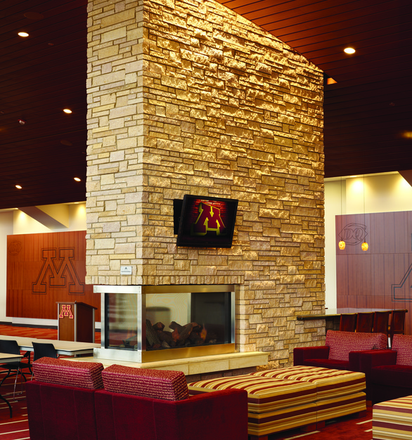 The mounts provided by Chief can mount any monitor to any type of background. Shown here is a monitor mounted to stone above a cozy fireplace within the stadium club lounge.