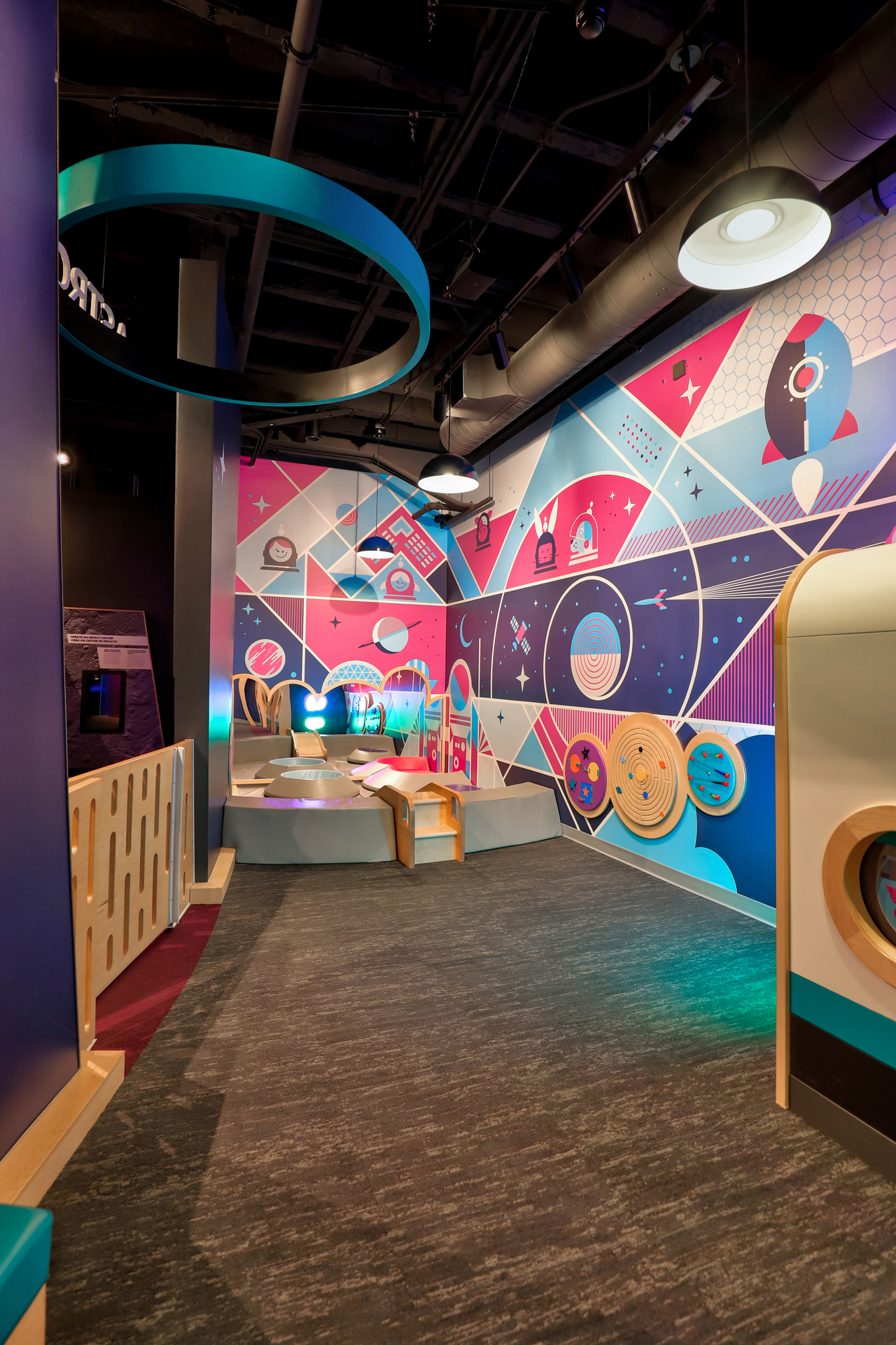 Explore space in this children's area with the bright wall graphics, custom lighting and interactive toys.