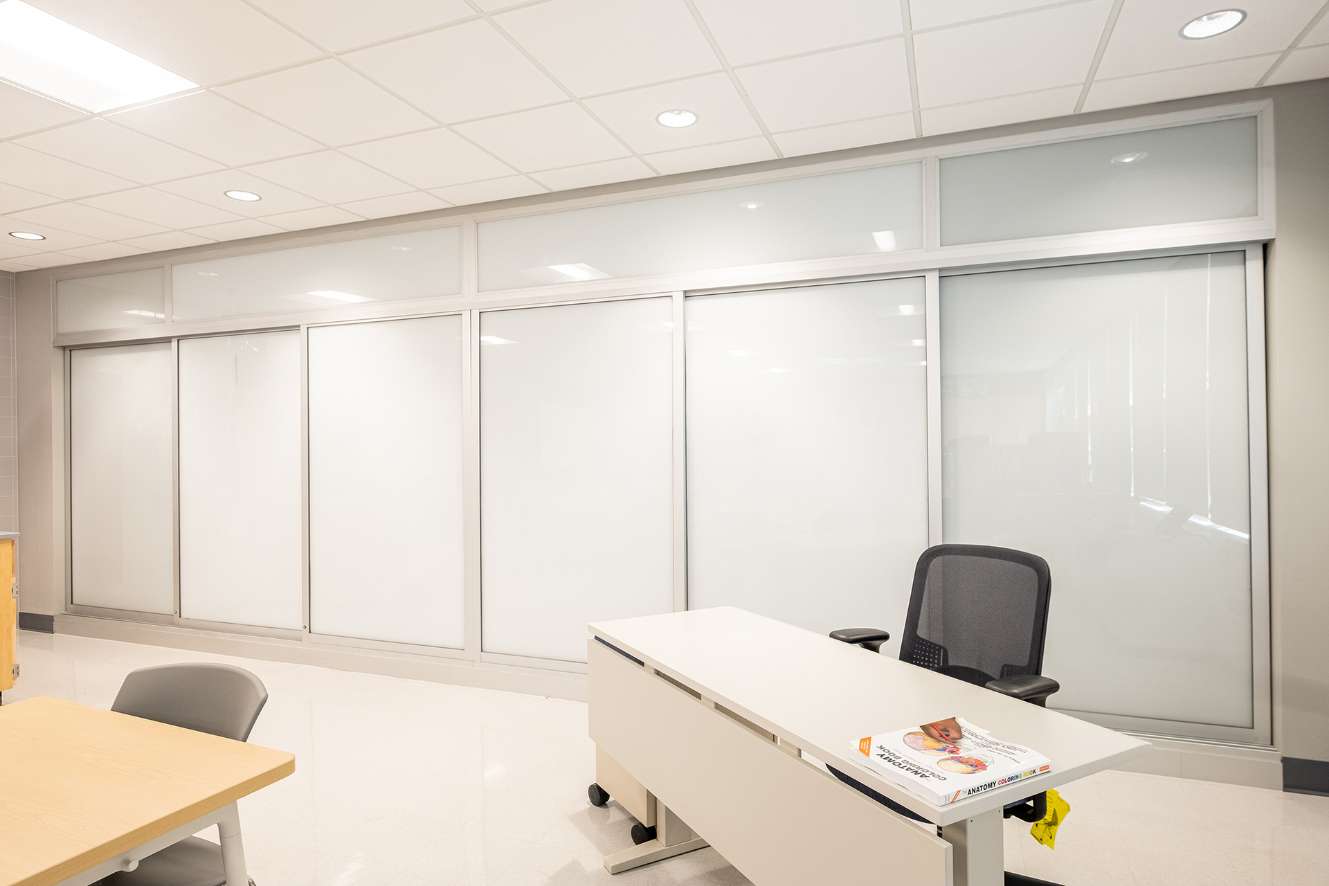 Sliding glass sliding doors create a versatile space for work and collaboration between peers and teachers.