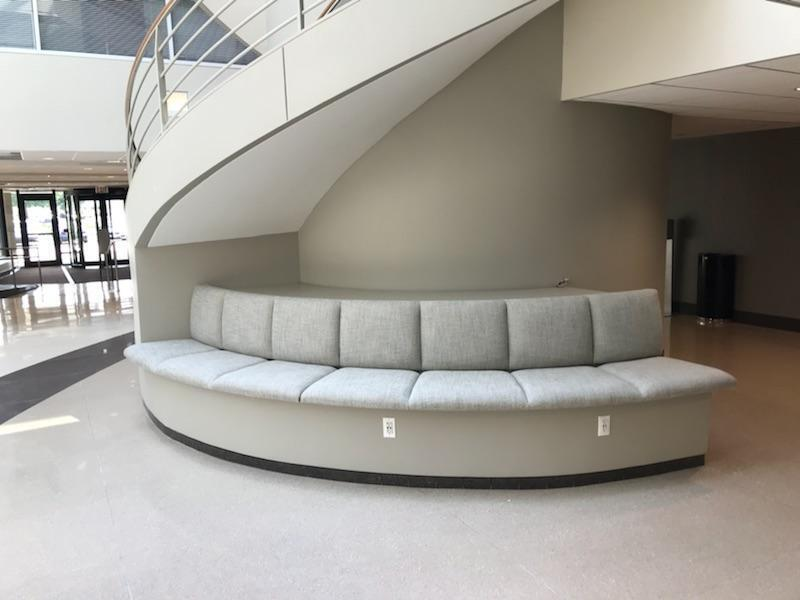 Contract Industries is available to make custom booth seating to fit any space. Seen here is a half-moon shape booth seating to perfectly wrap the pillar stairway it sits beneath.