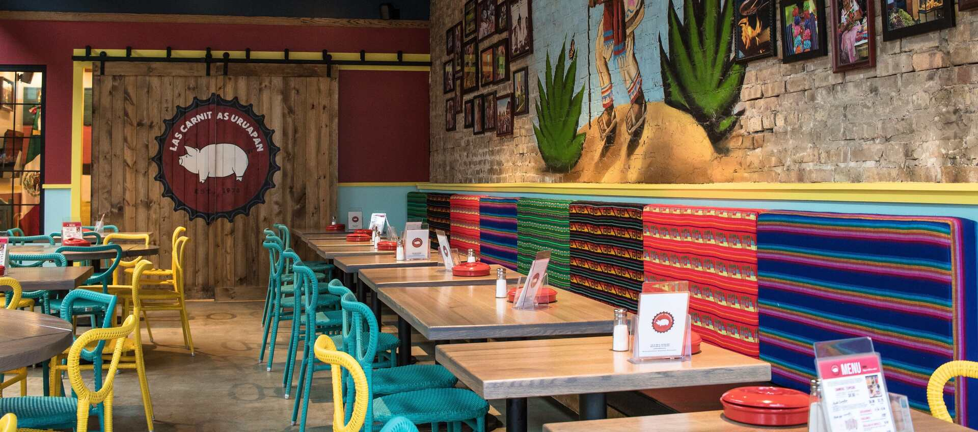 Colorful booth seating can be found at the Chicago location of Carnitas Uruapan provided by Contract Industries.