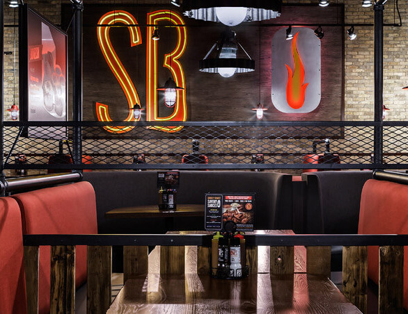 Red custom booth seating created by Contract Industries for Smokey Bones Bar and Grill in Chicago, Illinois.