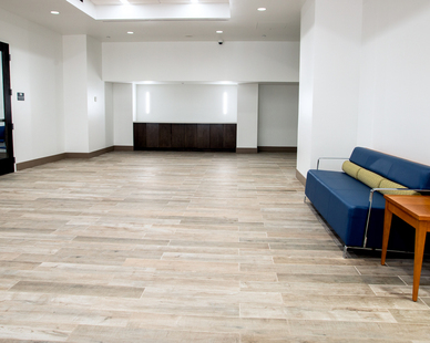 """For the main floor lobby and hallways, totaling 5,700 square feet, the firm chose Crossville's SpeakEasy 6""""x 36"""" planks. The stylish, contemporary tile features a washed wood look with subtle brown and grey undertones; the color is reminiscent of driftwood and therefore perfect for a beach community like Coral Gables."""