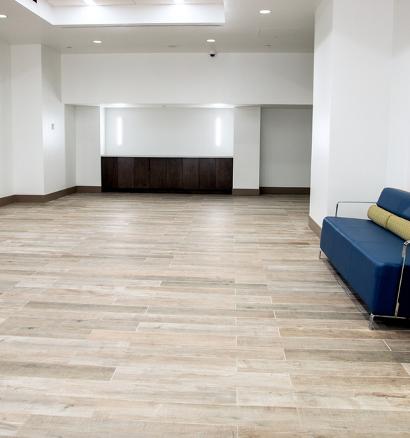 "For the main floor lobby and hallways, totaling 5,700 square feet, the firm chose Crossville's SpeakEasy 6""x 36"" planks. The stylish, contemporary tile features a washed wood look with subtle brown and grey undertones; the color is reminiscent of driftwood and therefore perfect for a beach community like Coral Gables."