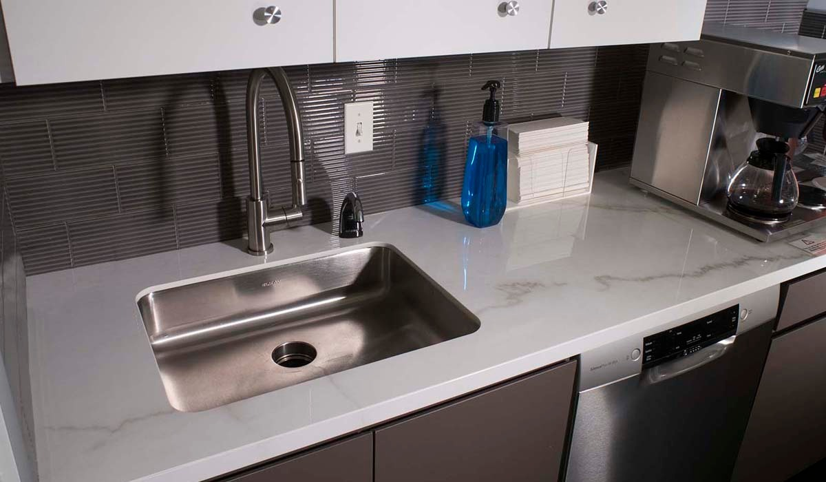 The white porcelain countertops from Crossville offer visual continuity with the area's white upper cabinets and striking contrast to the dark gray lower cabinets and backsplash.