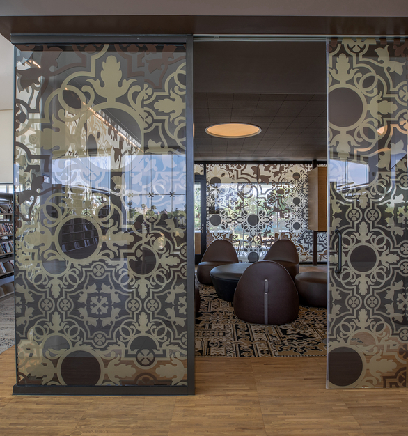 The custom graphic glass provided by Giroux Glass provides a decorative touch for the meeting room at the Lions Park Library.