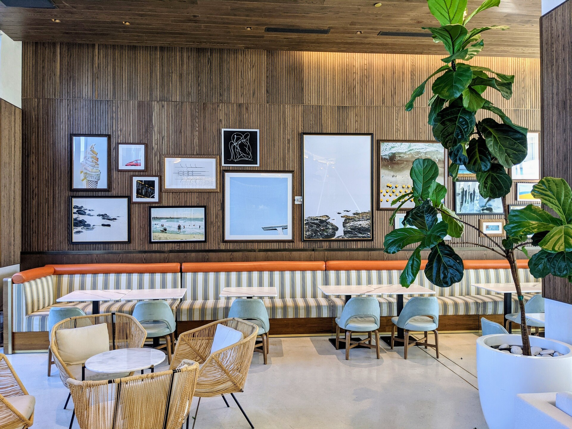 Sit down and enjoy a bite to eat at the hotel cafe.  They partnered with Surfacing Solutions and used their solid wood panels to create a gallery wall to showcase a variety of art.